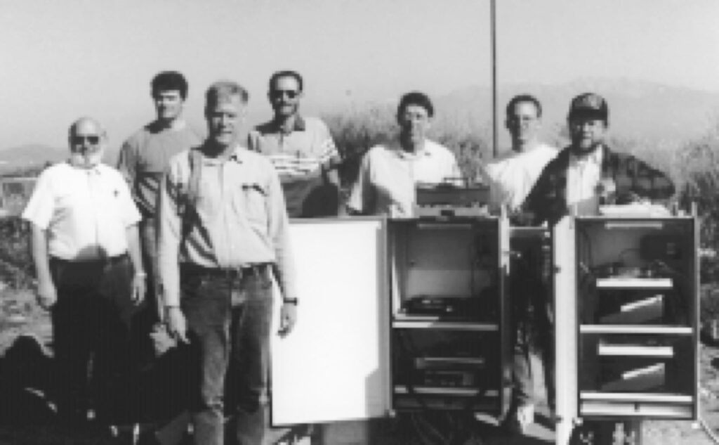 In front is Yehuda Bock, Scripps Institution of Oceanography. In the back from left to right are Gerald Stayner, Riverside County, Ken Hudnut, USGS, Gerald Doyle and Bill Young, Riverside County Flood and Water Conservation District, Keith Stark, Scripps, and an unidentified electrical contractor.